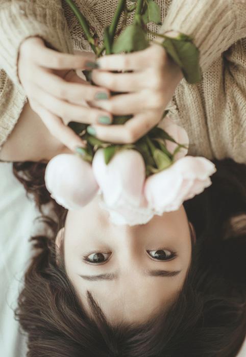 フリー 写真バラの花束を持って寝転ぶ女性