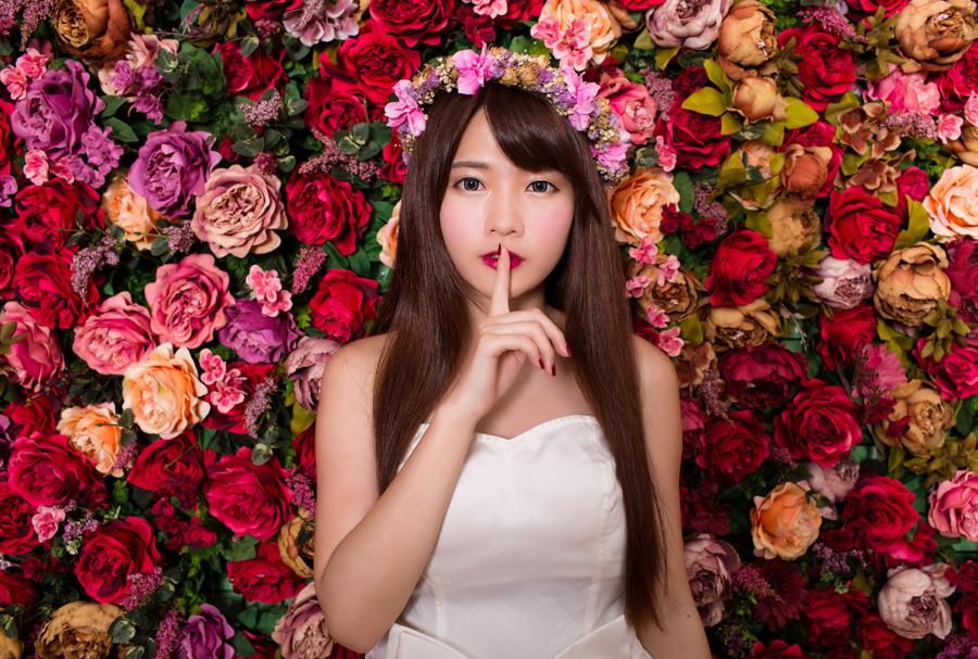 フリー 写真花の前で「しーっ」のポーズをとる花嫁