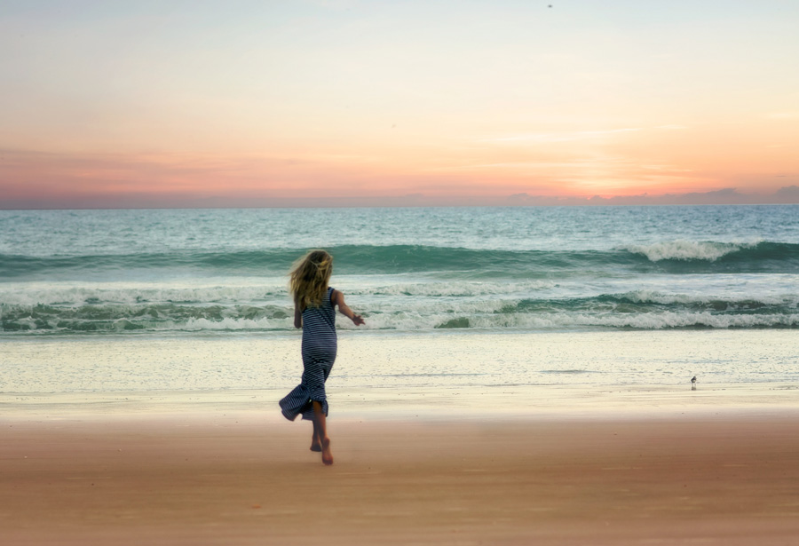 フリー 写真夕暮れの砂浜を走る女性