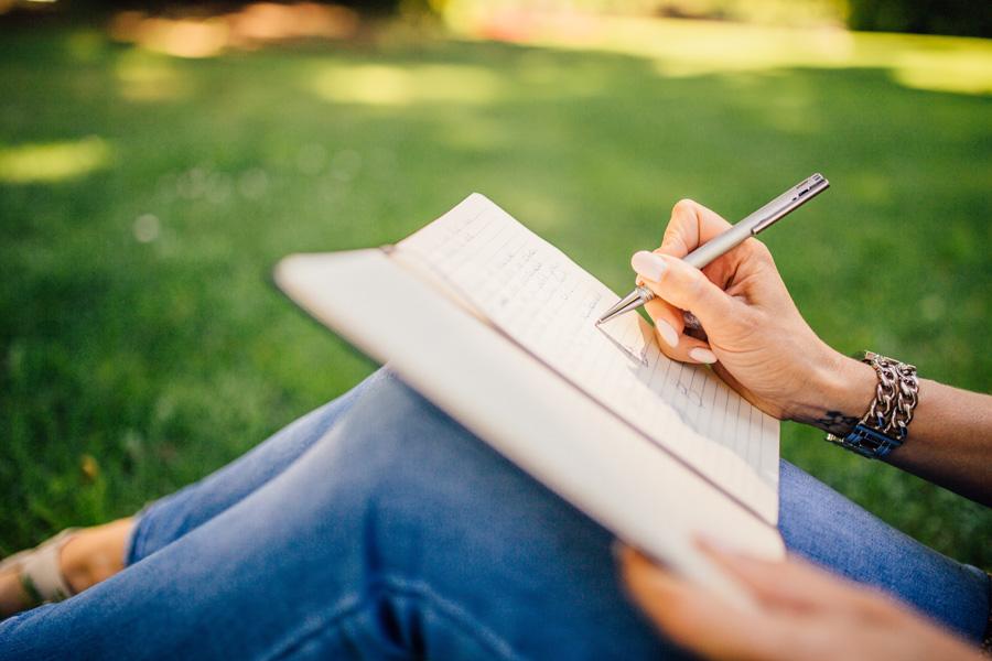 フリー 写真膝の上にノート置いて書く女性