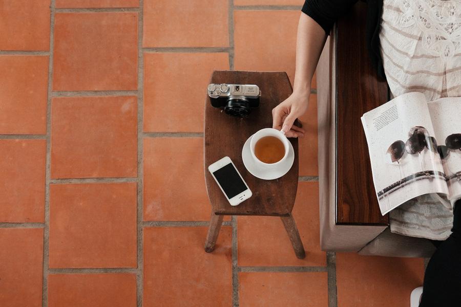 フリー 写真雑誌を読みながら紅茶に手を伸ばす女性