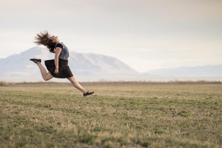 フリー 写真草むらでジャンプする外国人女性
