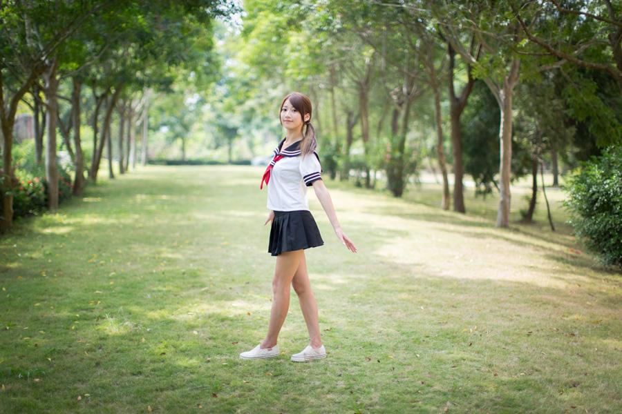 フリー 写真セーラー服姿で公園に立つ女子高生