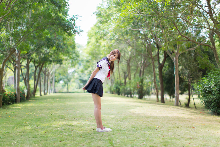 フリー 写真セーラー服姿で屈みながら振り返る女子学生