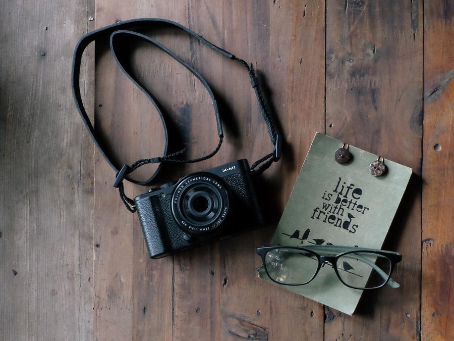 フリー 写真FUJIFILM X-M1のカメラとメモ帳と眼鏡