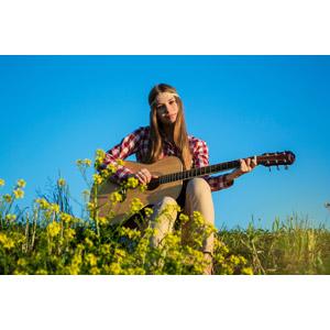 フリー写真, 人物, 女性, 外国人女性, 座る(地面), ヒッピーファッション, 楽器, 弦楽器, ギター, アコースティックギター, 音楽, 演奏する, 菜の花(アブラナ), 人と花