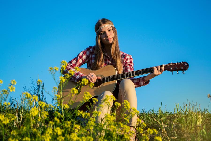 フリー 写真ヒッピーファッションでギターを弾く外国人女性
