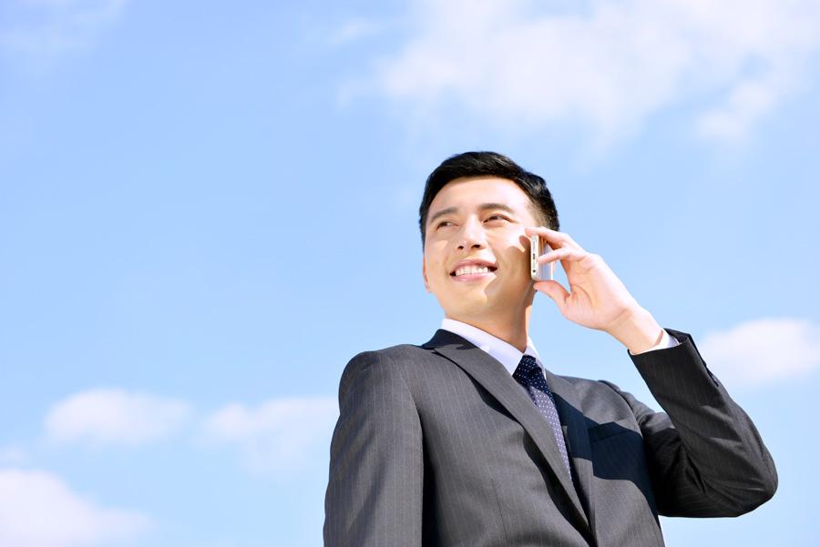 フリー 写真青空の下で携帯電話で話すビジネスマン