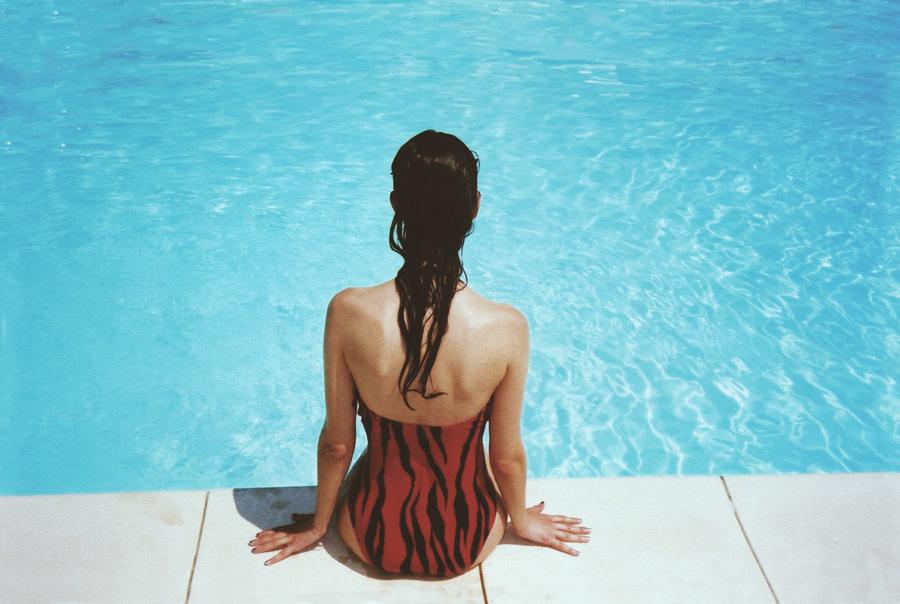 フリー 写真水着姿でプールサイドに座る女性の後ろ姿