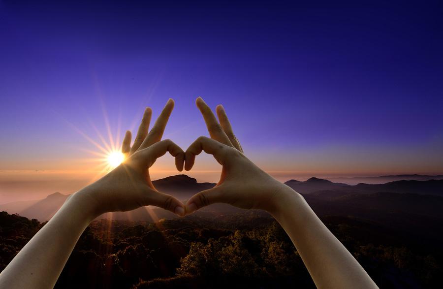 フリー 写真山の頂上から見る朝日と手で作るハート