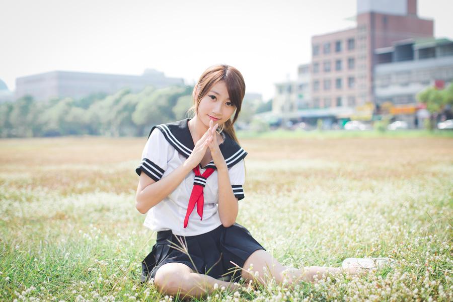 フリー 写真セーラー服姿で草むらの上に座る女子学生