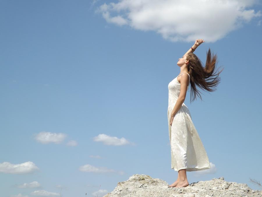 フリー 写真青空と岩の上に立つ外国人女性