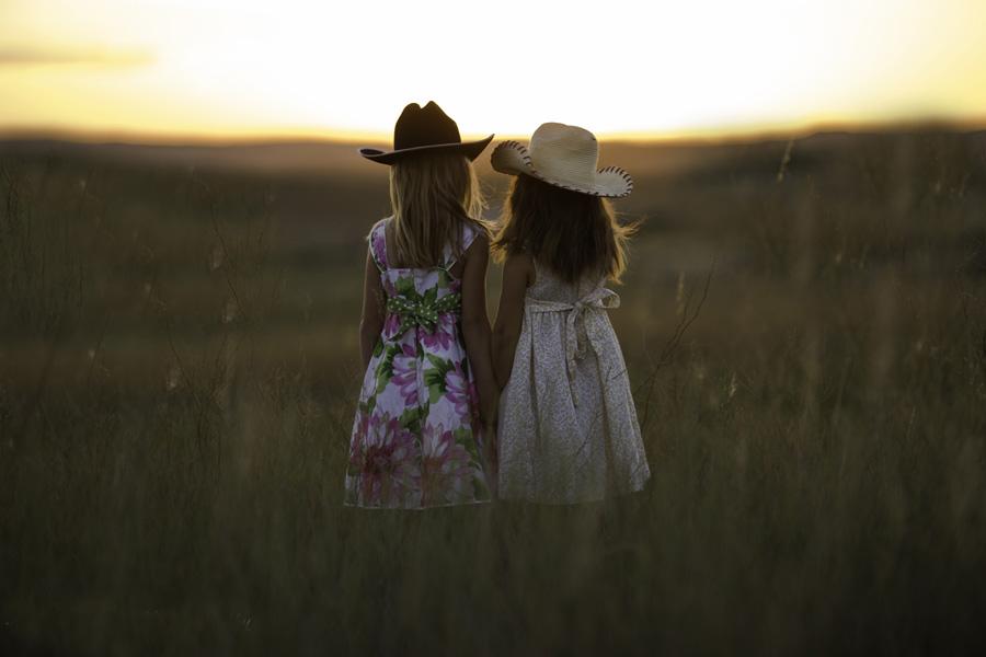 フリー 写真草むらに立って夕陽を眺める姉妹の後ろ姿