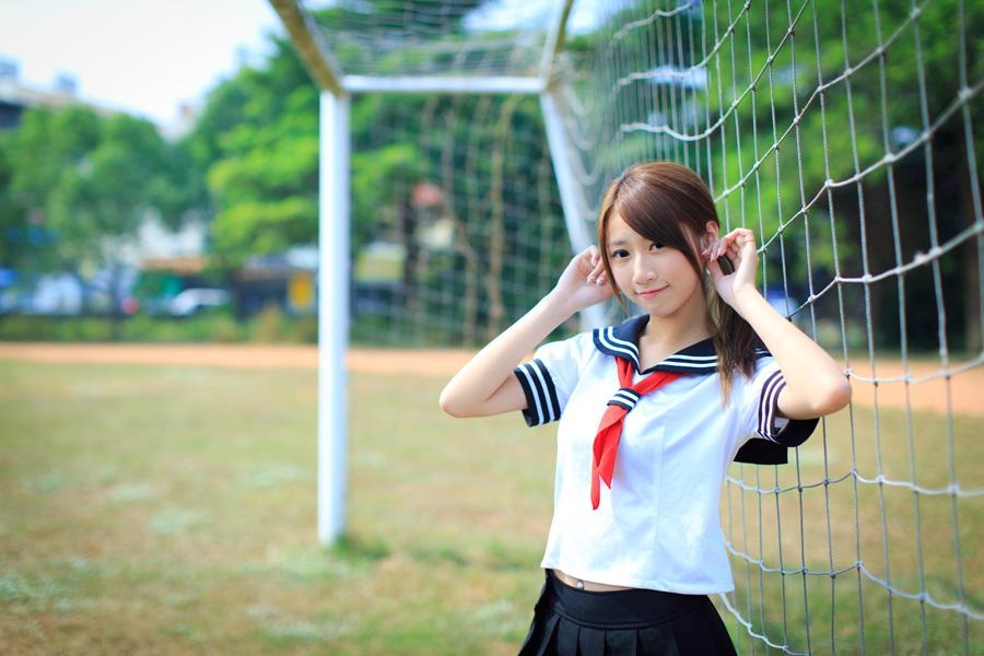 フリー 写真セーラー服姿でゴールネットの前に立つ女子学生