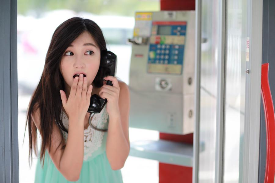 フリー 写真公衆電話で口を隠しながら驚く女性