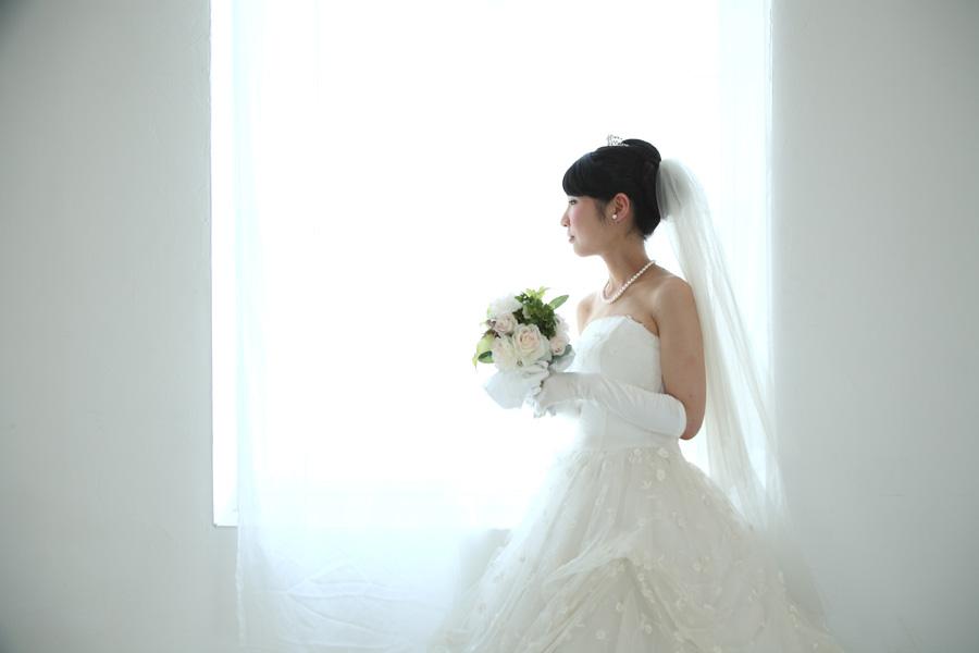 フリー 写真ウェディングドレス姿で窓辺に立つ女性