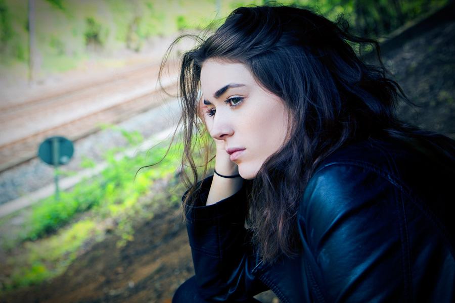 フリー 写真頬杖をついて線路を見つめる外国人女性
