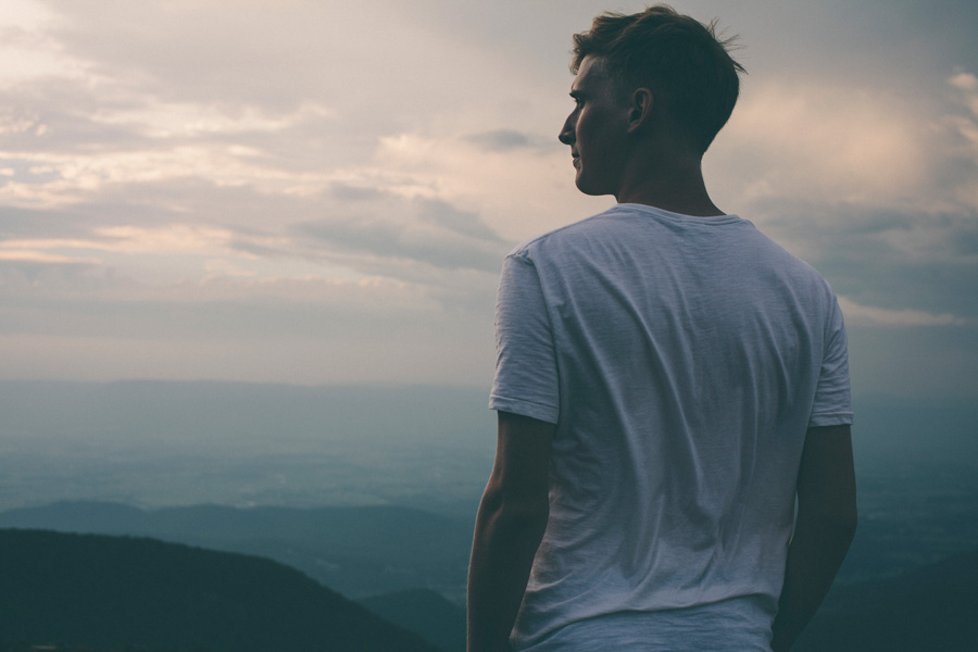 フリー 写真山の頂上に立つ外国人男性のポートレイト