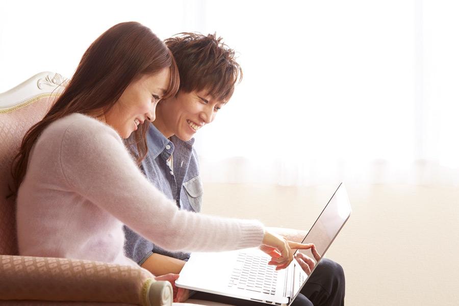 フリー 写真二人でノートパソコンを見て楽しむカップル