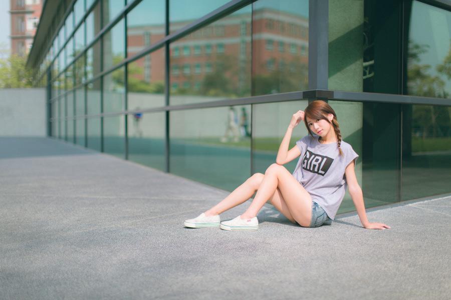 フリー 写真Tシャツとショートパンツ姿で建物の角に座る女性