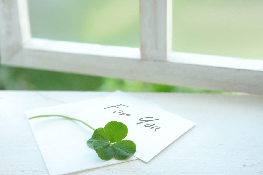 フリー 写真窓辺に置かれたメッセージカードと四つ葉のクローバー