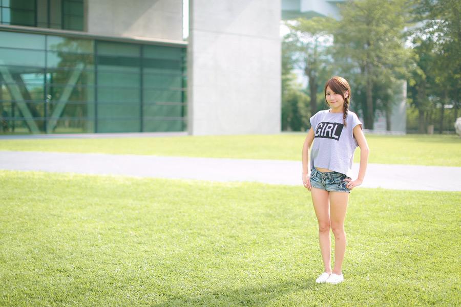 フリー 写真Tシャツとショートパンツ姿で芝生の上に立つ女性ポートレイト