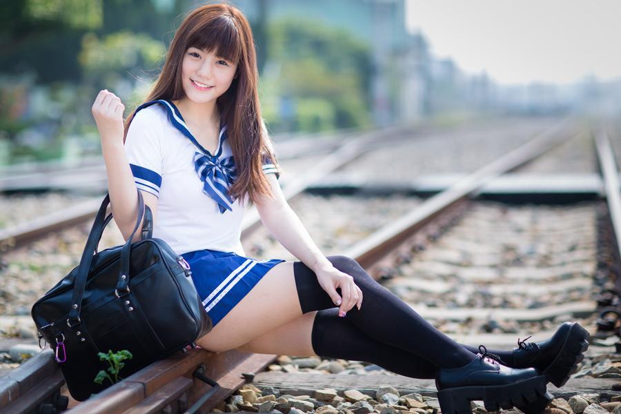 フリー 写真セーラー服姿で線路の上に座る女子学生