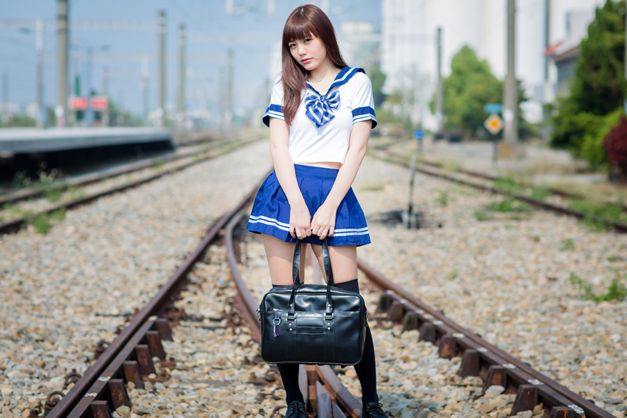 フリー 写真セーラー服姿で線路の上に立つ女子学生