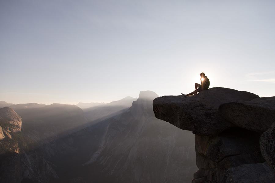 フリー 写真山の上の岩で休憩する人物と太陽光