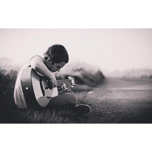 フリー写真, 人物, 子供, 男の子, 外国の男の子, 楽器, 弦楽器, ギター, アコースティックギター, 音楽, 演奏する, 座る(地面), あぐらをかく, 小道, 人と風景, モノクロ
