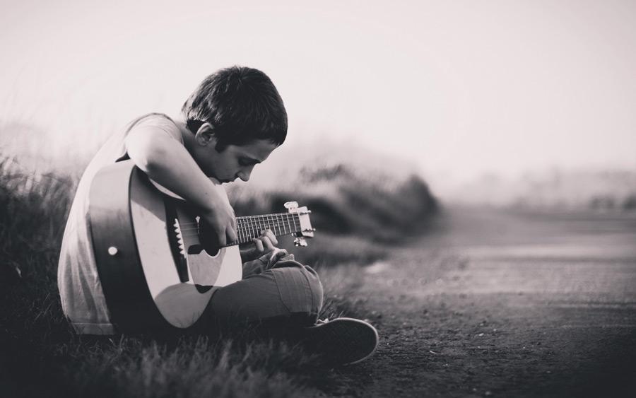 フリー写真 道のわきに座ってギターを弾く男の子