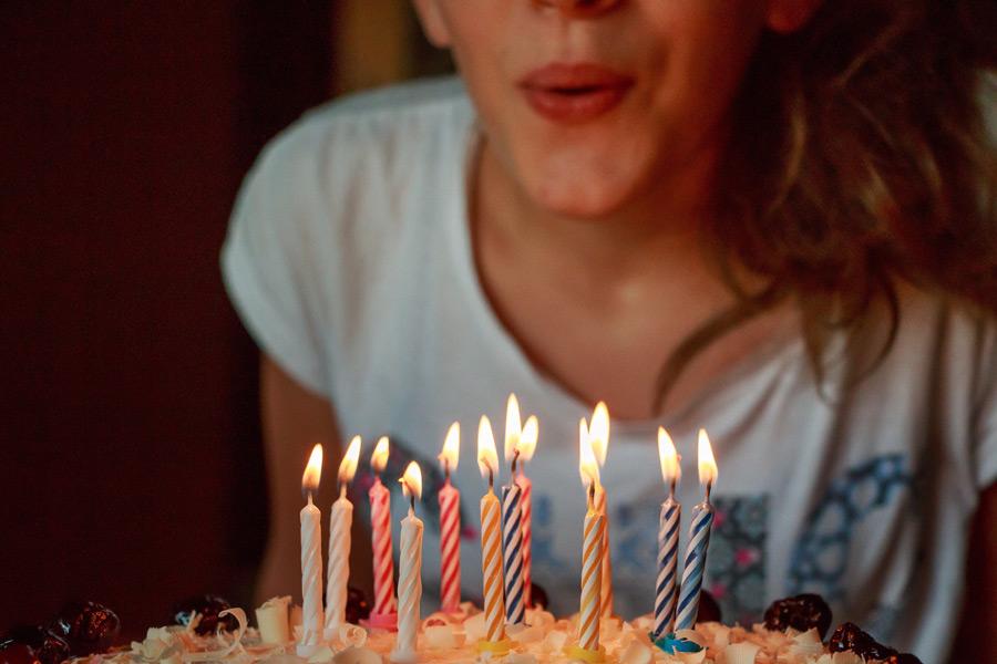 フリー写真 バースデーケーキのろうそくを吹き消そうとする女性