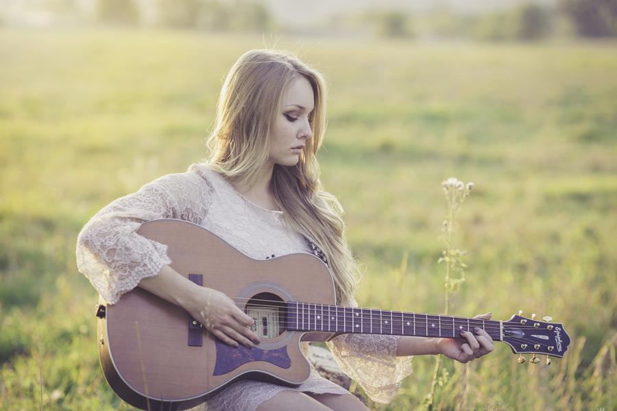フリー写真 草むらでギターを弾く外国人女性のポートレイト