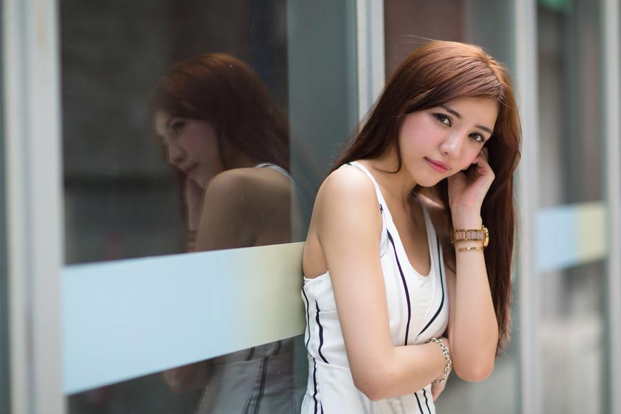 フリー写真 耳に手を当てながら窓の前に立つ女性