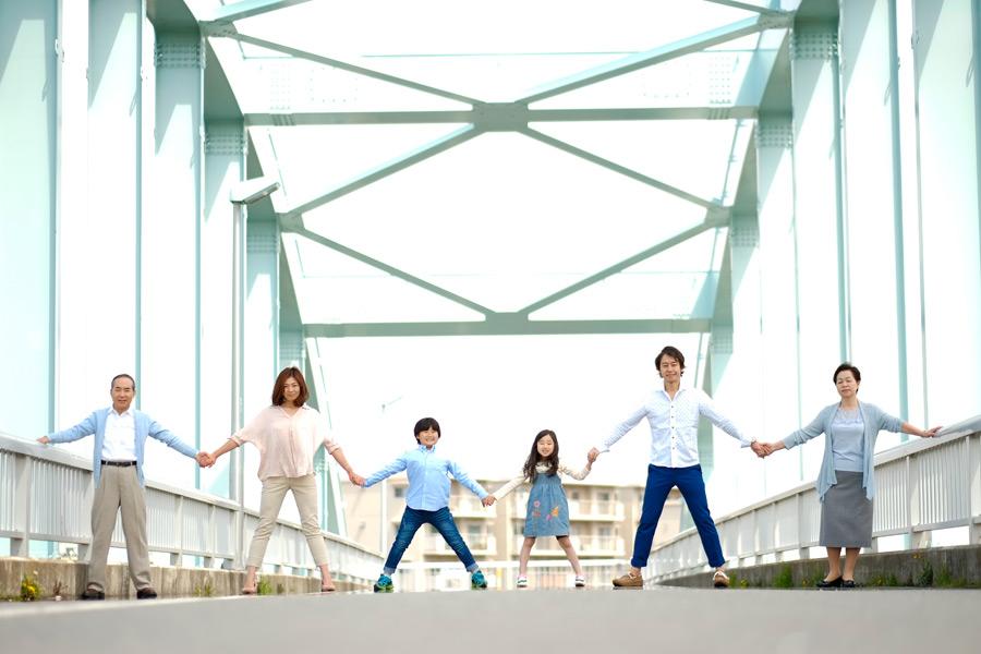 フリー写真 橋の上で手をつなぐ三世代家族