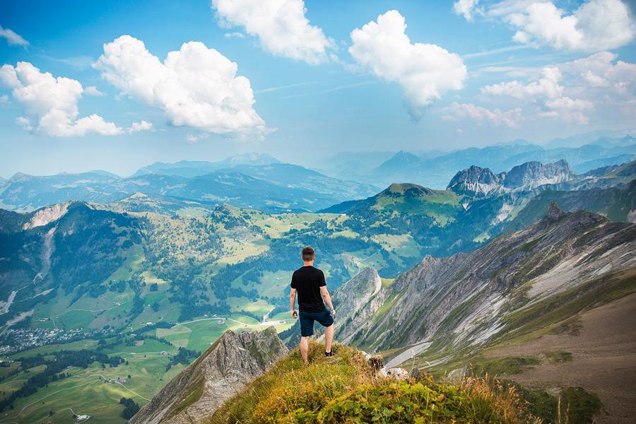 フリー写真 山の頂上から景色を眺める男性の後ろ姿