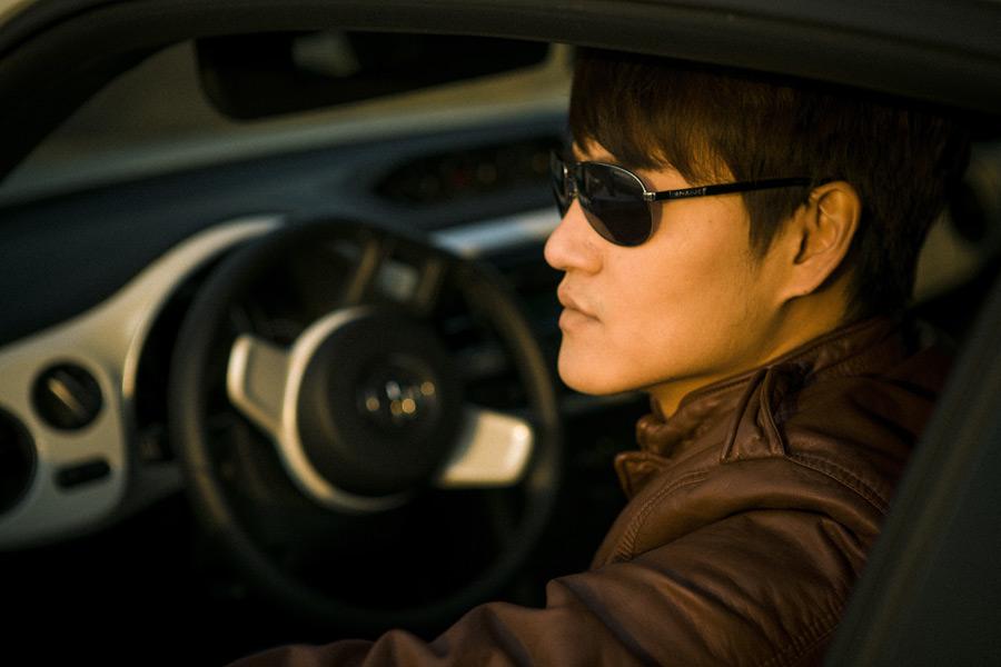 フリー写真 サングラスをかけて車に乗っている男性