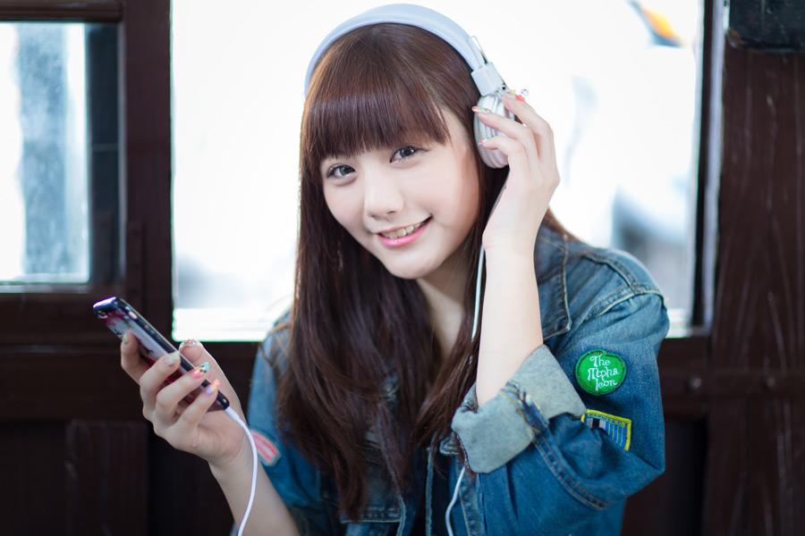 フリー写真 スマホで音楽を聴く女性のポートレイト