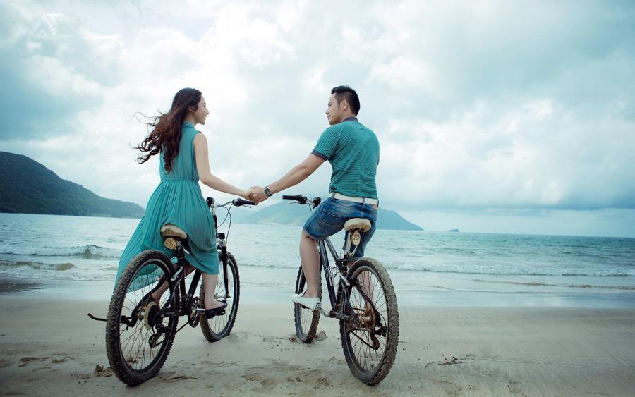フリー写真 自転車に乗って手をつなぐカップル