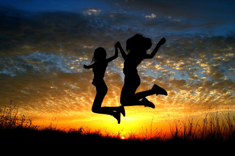 フリー写真 夕日と手をつないでジャンプする少女
