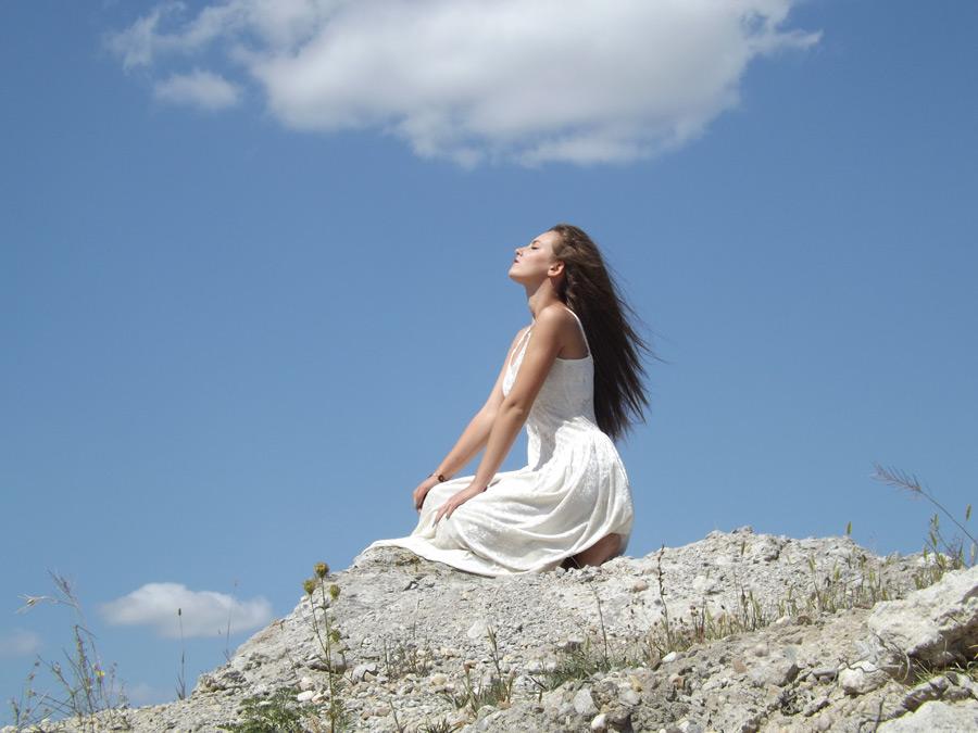 フリー写真 岩の上にしゃがんで目を閉じる外国人女性
