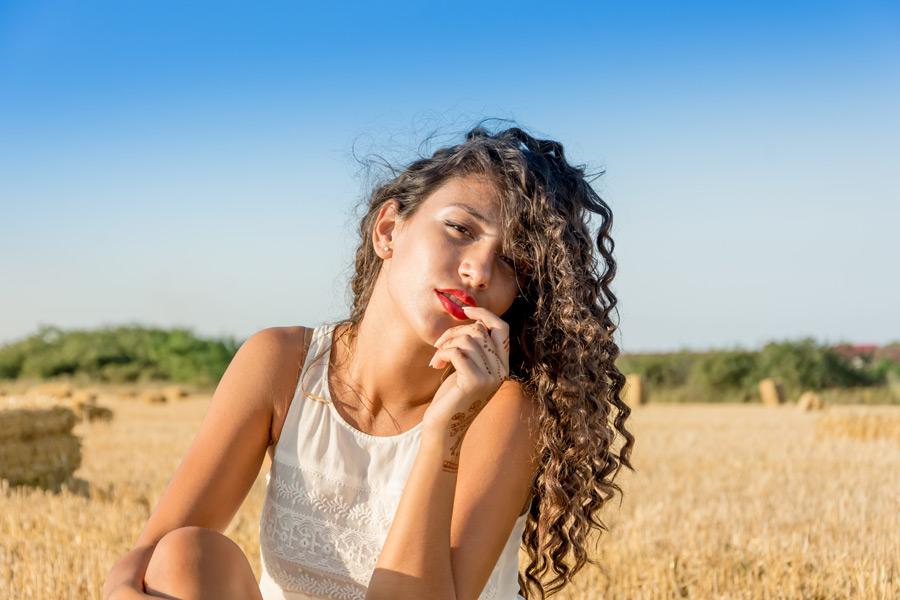 フリー写真 畑に座って唇に指を当てる外国人女性