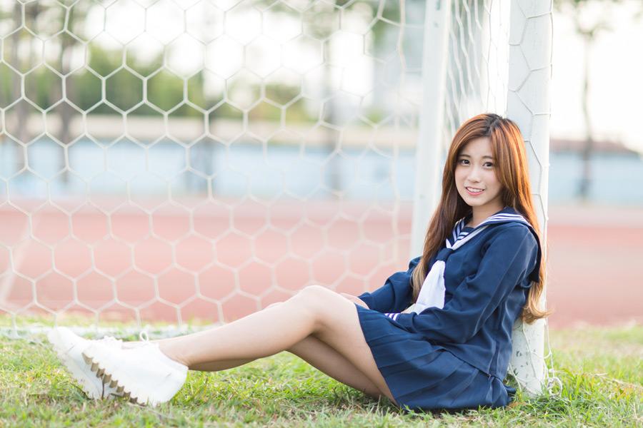 フリー写真 セーラー服姿でサッカーゴールの前に座る女子学生