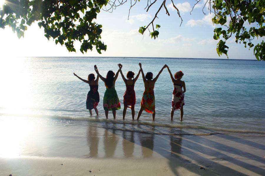 フリー写真 波打ち際でつないだ手を掲げる女性たち