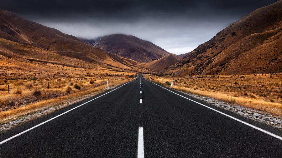 フリー写真 暗雲と山を抜ける道路