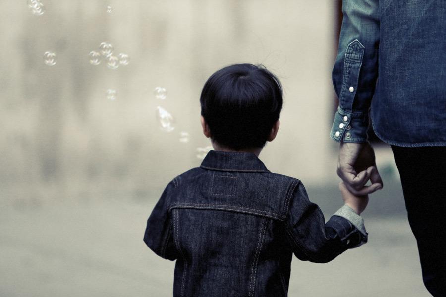 フリー写真 親と手をつないでしゃぼん玉を吹く男の子