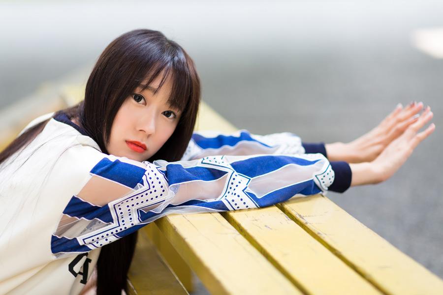 フリー写真 ベンチの上で手を伸ばす女性のポートレイト
