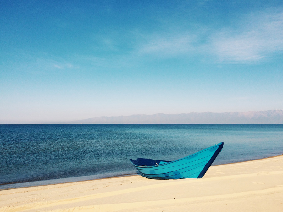 フリー写真 砂浜に上げられた青色のボートと海の風景