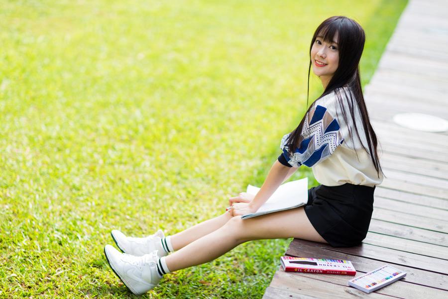フリー写真 スケッチブックを膝に乗せている女性