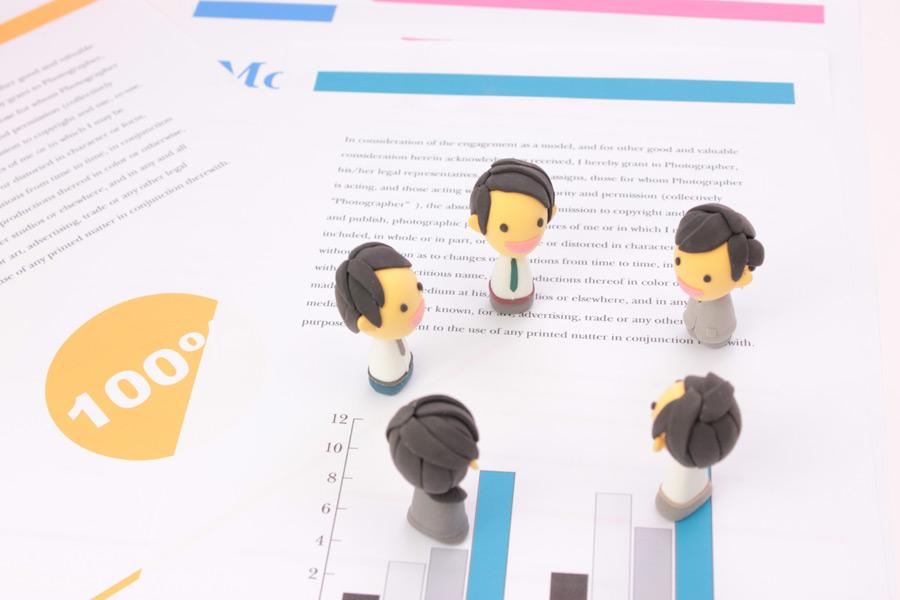 フリー写真 書類の上でミーティングしているビジネスパーソンの人形